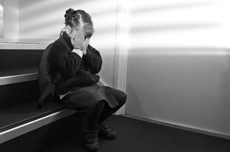 social outcast: Upset young girl (age 6-7) with school uniform and backpack sitting on a staircase, crying. Children education concept. copy space Stock Photo