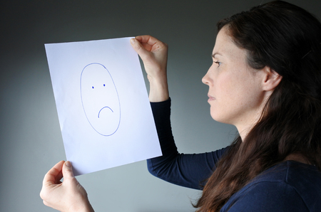 dissimulation: Young woman looks at a drawing with a sad face Stock Photo