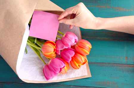 blanked: Woman hand place a blanked card , for your copy text, beside a Tulip flowers bouquet. Women lifestyle and holidays concept