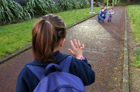 그녀의 어머니에 학교 웨이브 안녕에가는 어린 소녀 (나이 5-6). 사람들이 교육의 개념 스톡 콘텐츠