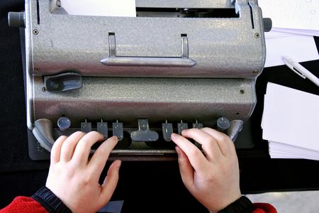 braile: vista en plano de manos de una persona ciega escribiendo en una m�quina de escribir en braille Foto de archivo
