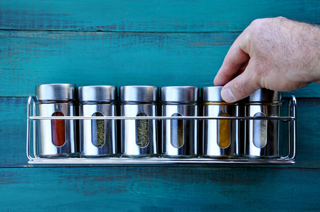 Chef hand returning spice into a spice rack. Food background. copy space 스톡 콘텐츠