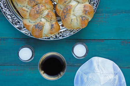 Flat lay view of Jewish Shabbat eve table meal with uncovered challah bread, Sabbath candles and Kiddush wine cup. copy space