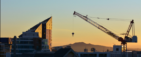 new construction: AUCKLAND - AUG 16 2016:Tower crane against Auckland skyline. A record number of over 50 cranes operating in the city building apartment blocks, office towers and other major urban public projects.
