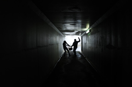 snatch: Silhouette of a man thief steals a bag from a woman in a dark tunnel. Violence against women concept. Real people, copy space