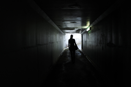 Silhouette of a young woman walks alone in a dark tunnel. Violence against women concept. Real people, copy space