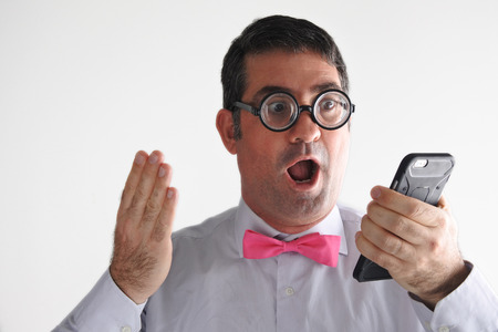 geeky: Surprised Geeky man receives a surprising message or phone call.   Communication concept. real people copy space