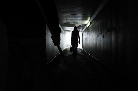 Silhouet van een man draagt een houten stok en volgt een jonge vrouw in een donkere tunnel. Geweld tegen vrouwen concept. Echte mensen, kopie ruimte Stockfoto