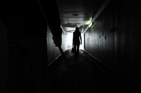 Silhouette of a man carries a wooden stick and follows a young woman in a dark tunnel. Violence against women concept. Real people, copy space
