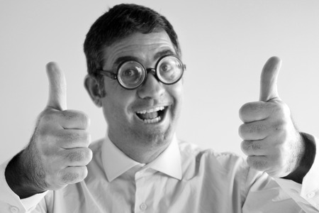 geeky: Thumbs up of a happy geeky man does thumbs up and looks at the camera. Men happiness concept. copy space (BW) Stock Photo