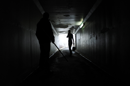 harassing: Silhouette of a man holds a  wooden stick harassing a woman in a dark tunnel. Violence against women concept. Real people, copy space