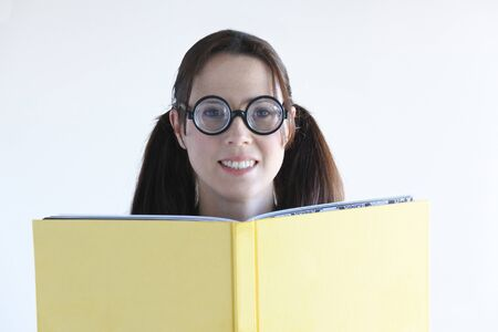 geeky: Geeky woman reads a book and looks at the camera. Women education concept. real people copy space