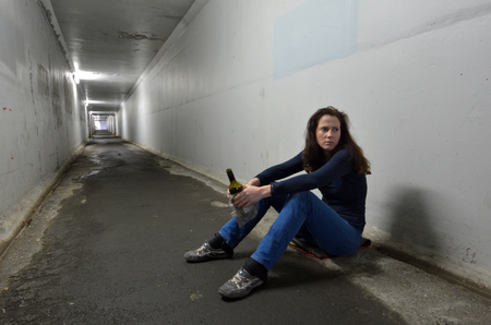 Drunk woman drinks alcohol in a tunnel. Women alcoholism concept. Real people, copy space