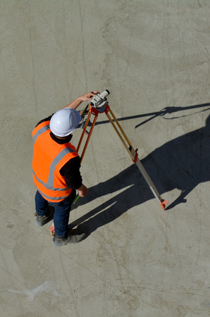 land surveying: Aerial view of unrecognizable land surveying in construction site. copy space. Vertical cover shoot