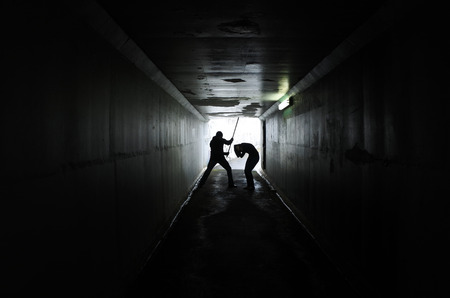 violent: Silhouette of a man beating up a woman with wooden stick in a dark tunnel. Violence against women concept. Real people, copy space Stock Photo