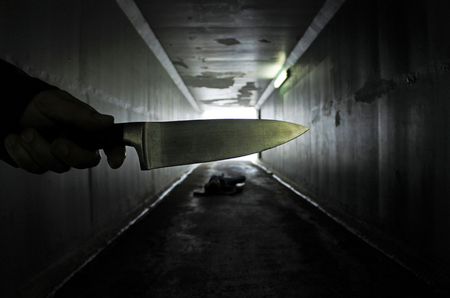 violent: Man hand holds a knife over a murder victim in a dark tunnel. Violence against women concept. Real people, copy space