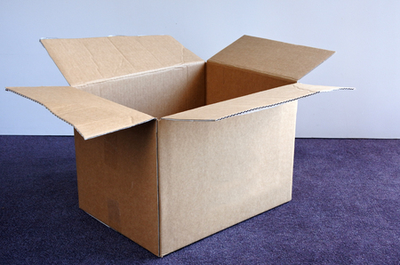 removals: An empty open cardboard box on a carpet and against a wall. Moving to a new place concept. copy space