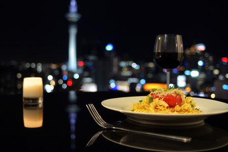 Dinner in front of Auckland city skyline at night. City life lifestyle concept. copy space
