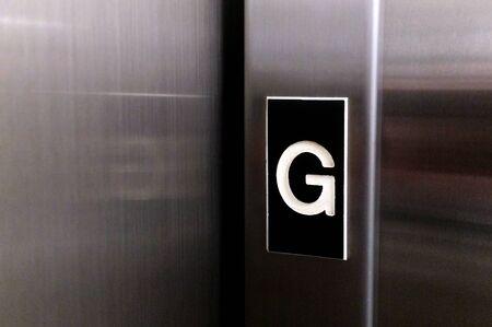 floor level: The letter G on elevator lift door indicating for ground floor level.