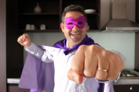 Happy superhero father in home kitchen looking and gesturing with his fist at the camera. Parenthood, fatherhood and father lifestyle concept. real people. copy space Stock Photo