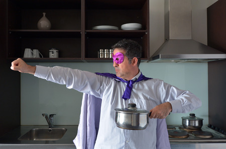 Superhero father cooking in home kitchen. Parenthood, fatherhood and father lifestyle concept. real people. copy space Stock Photo