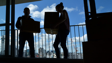 urban housing: Silhouette of a young couple moving into a new city home apartment carry boxes against urban city skyline. Real estate and housing concept. copy space