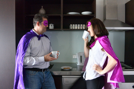 Superhero father and mother having a rest and coffee break in a home kitche.Parents, Parenthood and family lifestyle concept. real people. copy space