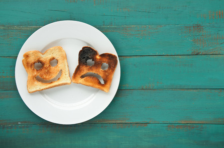 Flat lay view of two slices of toasted bread in a white plate. One is burned and one is well done. Relationship lifestyle concept. copy space Stock Photo