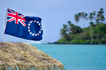 The flag of the Cook Islands, officially known as the Cook Islands Ensign, wave in the wind at Muri Lagoon in Rarotonga, Cook Islands. Stock Photo