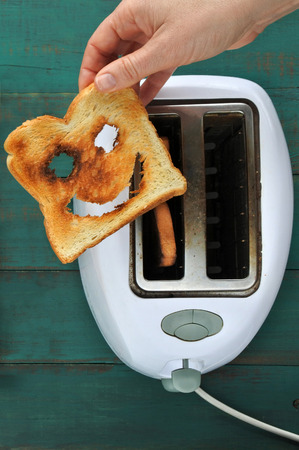 Flat lay view of hand holds one slices of toast bread against a  toaster. Happiness concept. copy space
