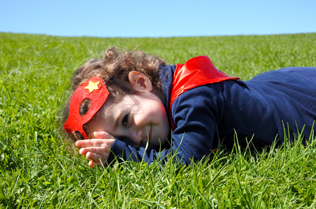 supergirl: Happy Superhero toddler lay on green grass. concept photo of Super hero, girl power, play pretend, childhood, imagination. Real people Stock Photo