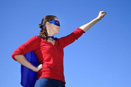 Superhero-moeder tegen blauwe hemelachtergrond met exemplaarruimte. conceptenfoto van Super held, meisjesmacht, ouderschap en moederschap. Echte mensen Stockfoto
