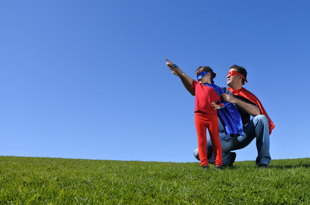 Superhero father shows his daughter how to be  a superhero against blue sky background with copy space. concept photo of Super hero, childhood, imagination, fatherhood and parenthood. Real people