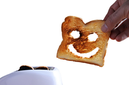 Hand holds one slices of good toast bread with a happy face against a  toaster. Happiness concept. copy space
