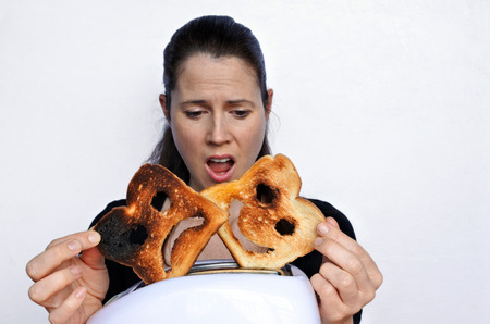 dissimulation: Shock woman looks a two different slices of toast bread one with happy face and one with sad face. Woman lifestyle concept. Real People. copy space