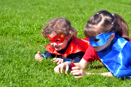 supergirl: Superhero sisters lay on green grass play outdoors. concept photo of Super hero, girl power, play pretend, childhood, imagination. Real people