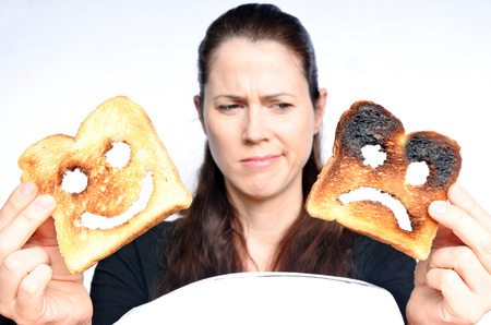 dissimulation: Woman looks a two different slices of toast bread one with happy face and one with sad face. Woman lifestyle concept. Real People. copy space