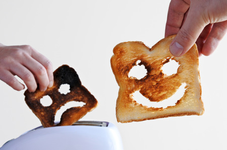 Man hand holds one slices of toast bread with happy face against a toaster and woman hand holds a  burnt toast with sad face.Couple relationship concept. copy space Stock Photo