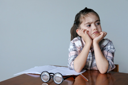 reluctance: Upset child (girl age 6 -7) do not want to do homework. Children childhood education concept Stock Photo