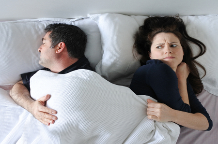 Man (age 35 -4 5) hogging the blanket from his woman in bed (Age 30-40) Couple lifestyle. Real people. copy space Stock Photo