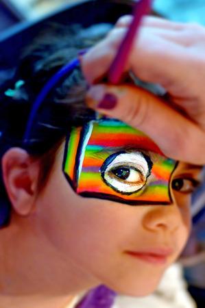 Jong meisje (leeftijd 6-7) krijgt haar gezicht geschilderd in de kleuren van de regenboog rond haar oog door schminken kunstenaar. Stockfoto