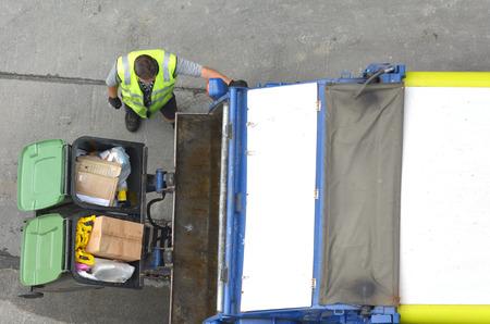 Luchtfoto van de niet-erkende Garbage man het laden vuilniswagen. Afval en recycling concept met een kopie ruimte