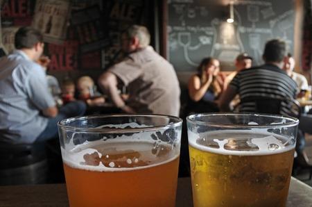 Dos vasos de cerveza en una mesa de bar con la figura borrosa de la gente que bebe alcohol en el fondo Foto de archivo