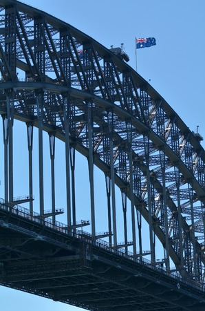 new south wales: The National flag of Australia blows on Sydney Harbour Bridge in Sydney New South Wales,  Australia.