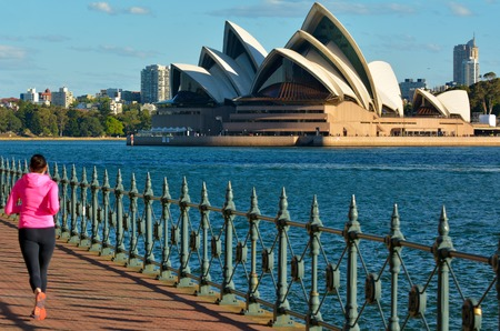 new south wales: Unrecognisable woman runs in North Sydney waterfront against Sydney Opera House at sunset in Sydney New South Wales, Australia