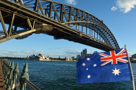 The National flag of Australia flies under Sydney Harbour Bridge and the Opera House in Sydney, Australia Editorial