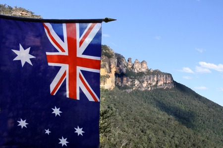 The National flag of Australia flies beside the Three Sisters rock formation in the Blue Mountains of New South Wales, Australia, on the north escarpment of the Jamison Valley. Stock Photo