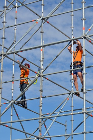 buildingsite: SYDNEY - OCT 19 2016:Scaffold builders at work.OSHA statistics report that about 28% of the scaffold accidents that occur are the result of construction deficiencies. Editorial