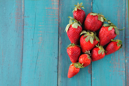 Group of fresh red strawberries in a shape of one big red strawberry on a wooden table. Food background with copy space