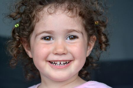 space age: Happy curly smiley child (girl age 02) . Childhood concept. Real people. copy space